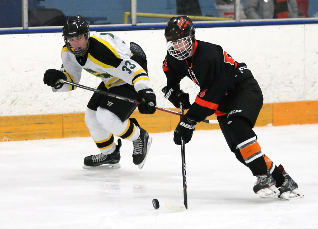 . Randy Meyers - The Morning Journal<br> North Olmsted\'s Riley Vertosnik stops a rolling puck in front of Tyler Waldecki of Amherst during the first period of a Southwestern Conference tournament semifinal on Jan. 15.