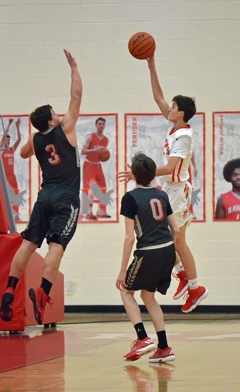 . Paul DiCicco - The News-Herald  Hawken\'s Charlie Ross, shoots over an outstretched Robbie Mulh in the third quarter on Feb 1.