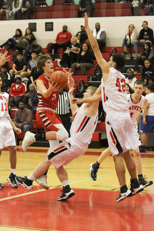 . Barry Booher - The News-Herald Jake Reid goes to the basket against Harvey\'s Zach Guajardo and (42) Marc Berry.