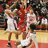 Barry Booher - The News-Herald<br /> Perry's Jacob Allen is defended by Harvey's (left) Desmond Taylor and (right) Tyrelle Early.