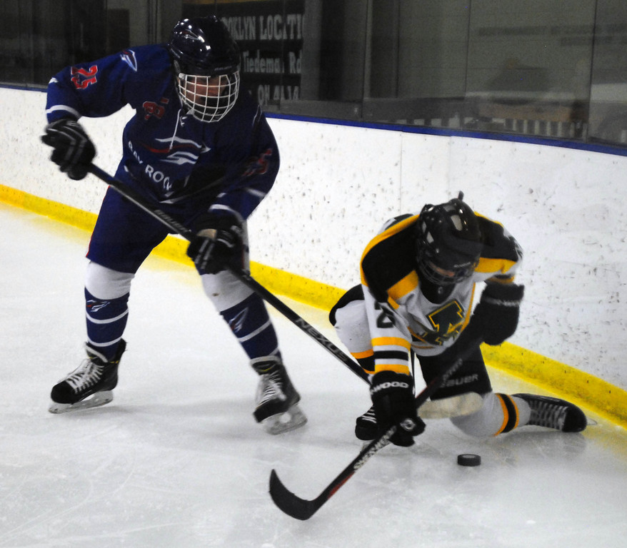 . Jon Behm - The Morning Journal<br> Bay senior Jake Gaudino and Amherst sophomore Jacob Kramer fight for possession of the puck during the first period of a Baron Cup II quarterfinal on Feb. 5 at Brooklyn\'s John M. Coyne Recreation Center.