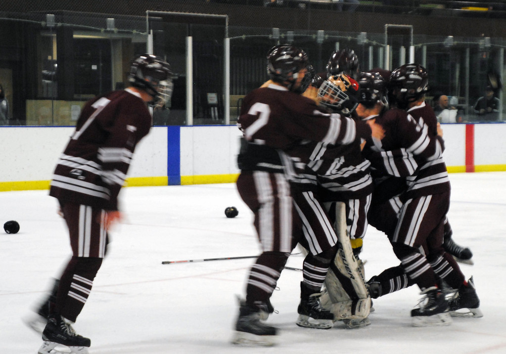 . Jon Behm - The Morning Journal<br> Rocky River players skate in to celebrate with senior goalie Ryan Dunning after claiming the Baron Cup I title with a 2-1 win over Shaker Heights on Feb. 11 at Brooklyn\'s John M. Coyne Recreation Center.