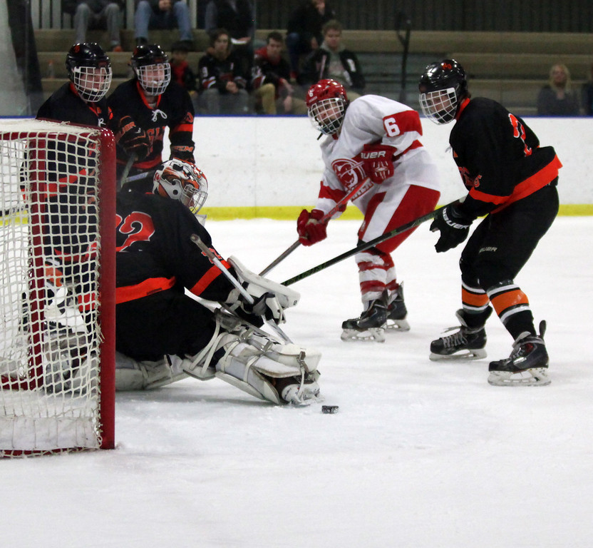 . Randy Meyers - The Morning Journal North Olmsted gaolie Ryan Godin  deflects a shot by Shaker\'s Geoff Grossman- McKee during the first period  of the Baron Cup finals on Sunday.