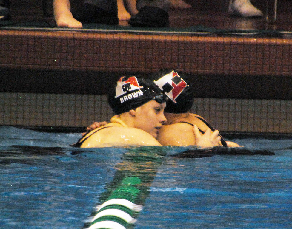 . Jon Behm - The Morning Journal<br> Hawken\'s Portia Del Rio Brown, left, and Abby Hay hug following the 200 Individual Medley at the Division II Northeast District meet on Feb. 16 at Cleveland State\'s Robert F. Busbey Natatorium. Brown took first in the race, with Hay finishing second.