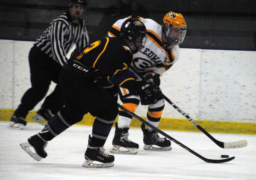 . Jon Behm - The Morning Journal<br> Avon\'s Cole Emerine skates in to defend St. Edward\'s Andrew Tomer during the first period of a Brooklyn District sectional semifinal on Feb. 18 at Brooklyn\'s John M. Coyne Recreation Center.