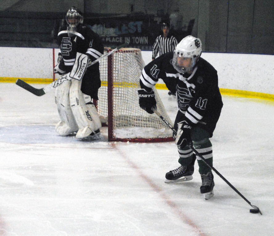. Jon Behm - The Morning Journal<br> Elyria Catholic senior Drew Beck looks to clear the puck against Normandy during the first period of a Brooklyn District sectional semifinal on Feb. 18 at Brooklyn\'s John M. Coyne Recreation Center.