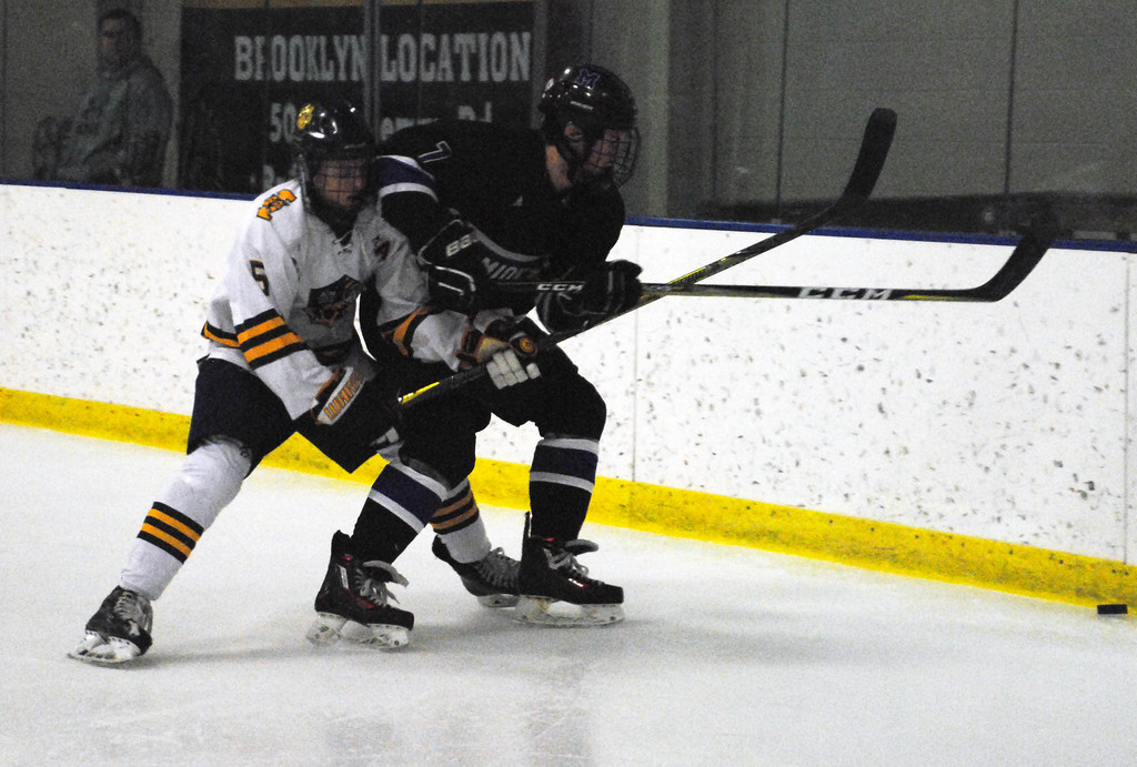 . Jon Behm - The Morning Journal<br> Midview\'s Robby Rodgers tries to beat St. Ignatius\' Michael Boehm to a loose puck during the first period of a Brooklyn District sectional final on Feb. 20 at Brooklyn\'s John M. Coyne Recreation Center.