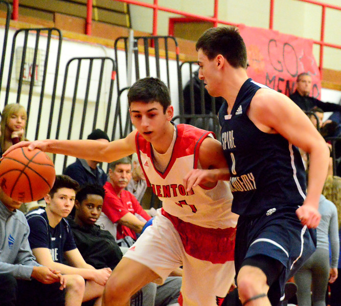 Brittany Chay - The News-Herald<br /> Mentor's Matt Koski dribbles against a Spire defender during the Cardinals' victory on Feb. 25.