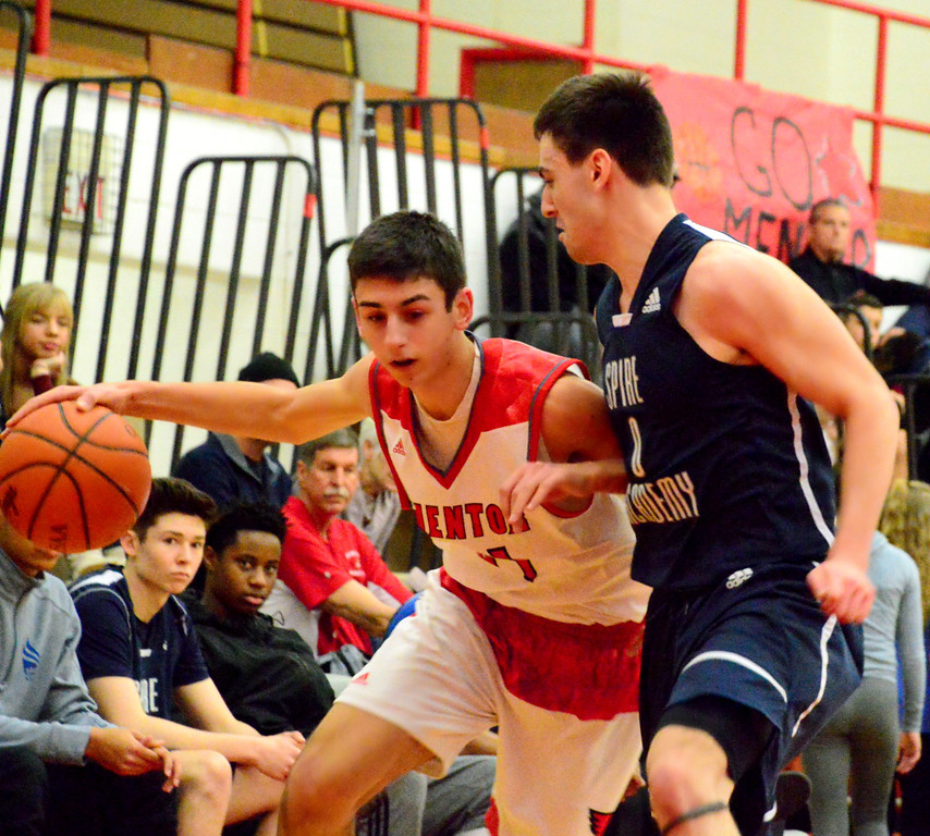 . Brittany Chay - The News-Herald Mentor\'s Matt Koski dribbles against a Spire defender during the Cardinals\' victory on Feb. 25.