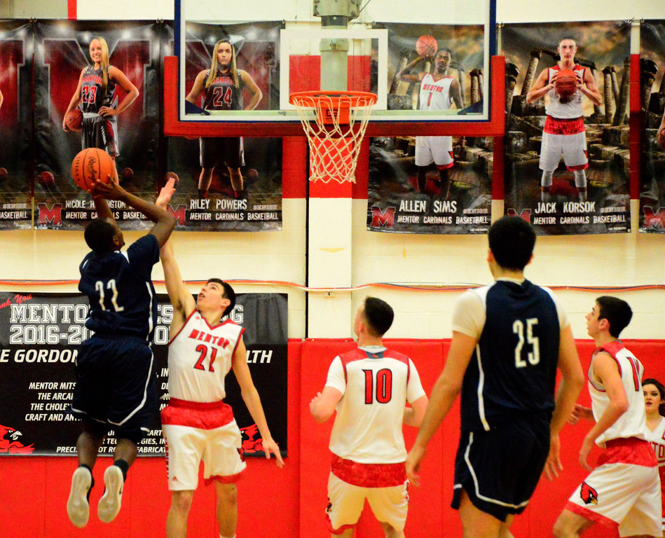 . Brittany Chay - The News-Herald Spire\'s Darius Jones shoots over Mentor\'s Shane Zalba during the Cardinals\' victory on Feb. 25.