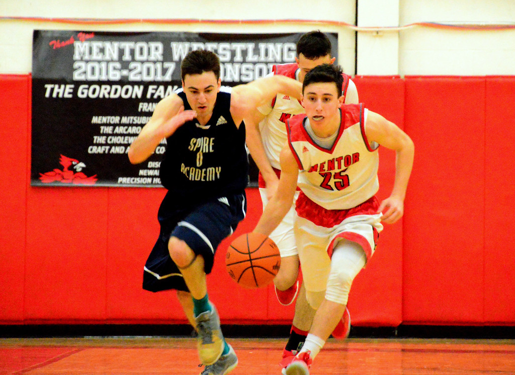 . Brittany Chay - The News-Herald Mentor\'s Luke Floriea dribbles ahead of Spire\'s Jesse Davis during the Cardinals\' victory on Feb. 25.