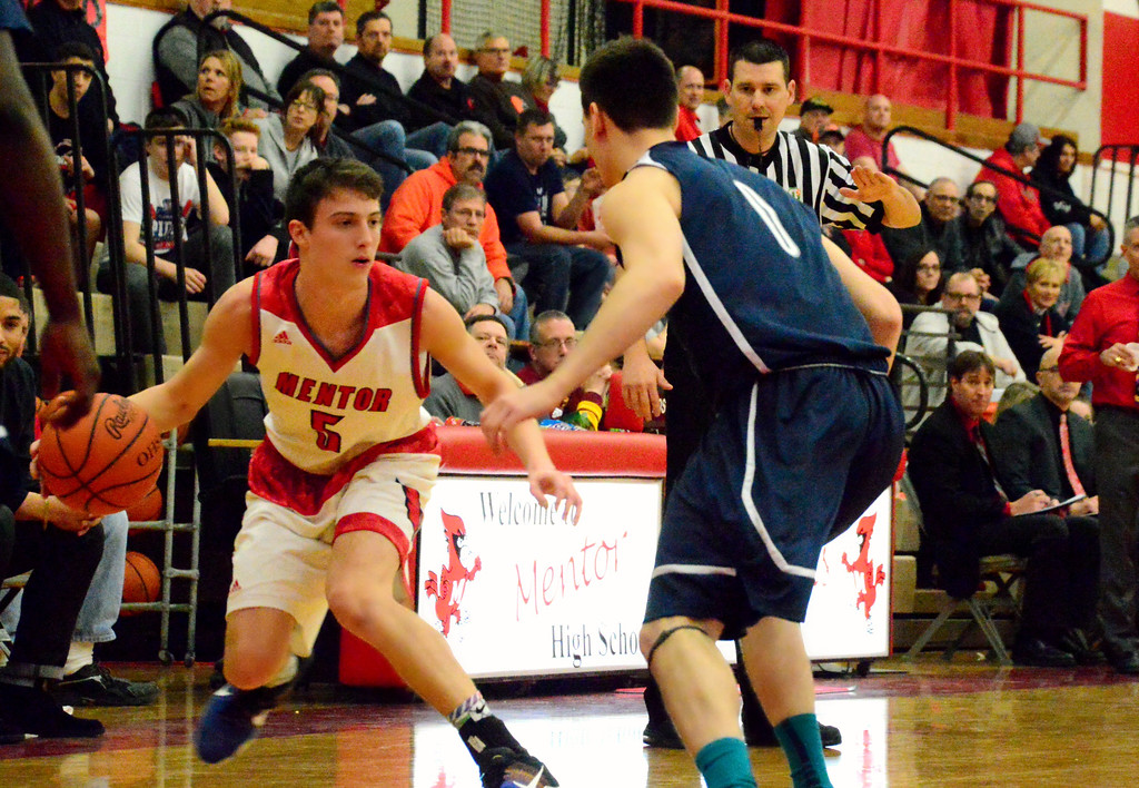 . Brittany Chay - The News-Herald Mentor\'s Jack Korsok dribbles against Spire during the Cardinals\' victory on Feb. 25.