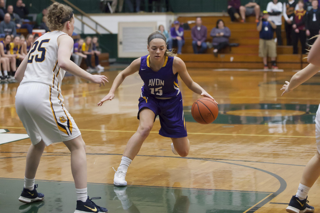 . Jen Forbus - The Morning Journal Avon\'s Maggie Beatty dribbles toward the basket and defender Sarah Balfour of Olmsted Falls.