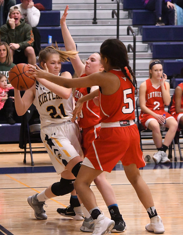 . Eric Bonzar�The Morning Journal<br> Kirtland\'s Lauren Lutz (21) tries to move the ball up court past the defense of Lutheran West\'s Jashauna Harris (5) and Paris Mather.