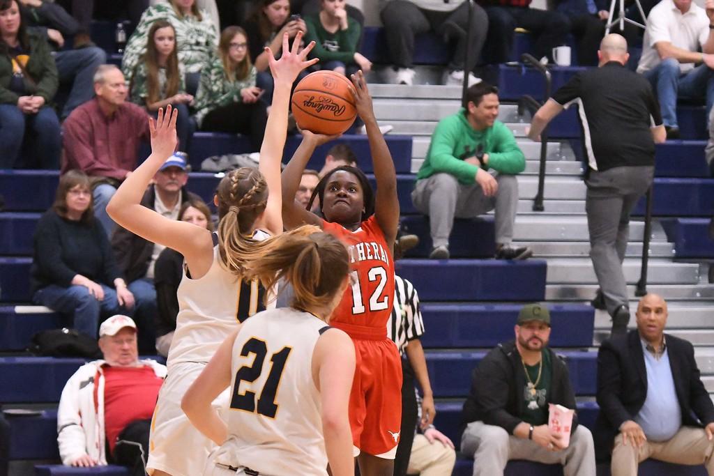 . Eric Bonzar�The Morning Journal<br> Lutheran West\'s Raiyah Johnson (12) shoots over Kirtland defender Lauren Snyder (0).
