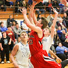 Barry Booher - The News-Herald<br /> Chardon's Alex Sulka attempts a layup past the defense of Madison's Marcus Horton and Zach Guyer (20). Madison won, 69-55.