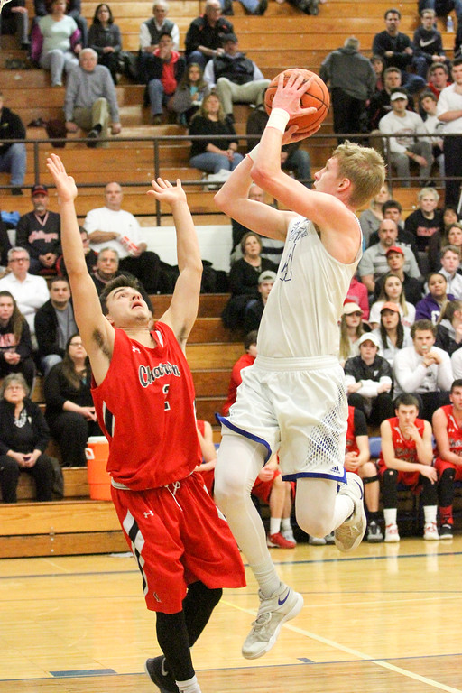 . Barry Booher - The News-Herald Madison\'s Corbin Anthony shoots over Chardon\'s Mike Laudato. Madison won, 69-55.