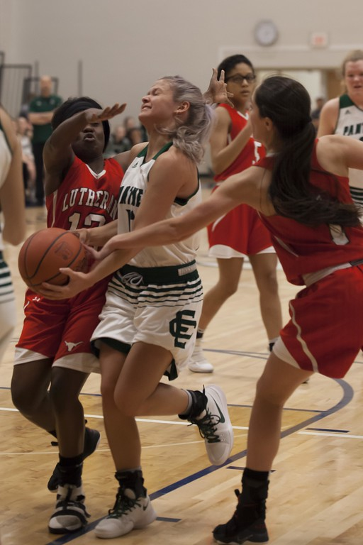 . Jen Forbus - The Morning Journal<br> Faith Williams of Elyria Catholic tries to push her way through defense from Lutheran West\'s Abriana Rondin, right, and Raiyah Johnson on March 3.