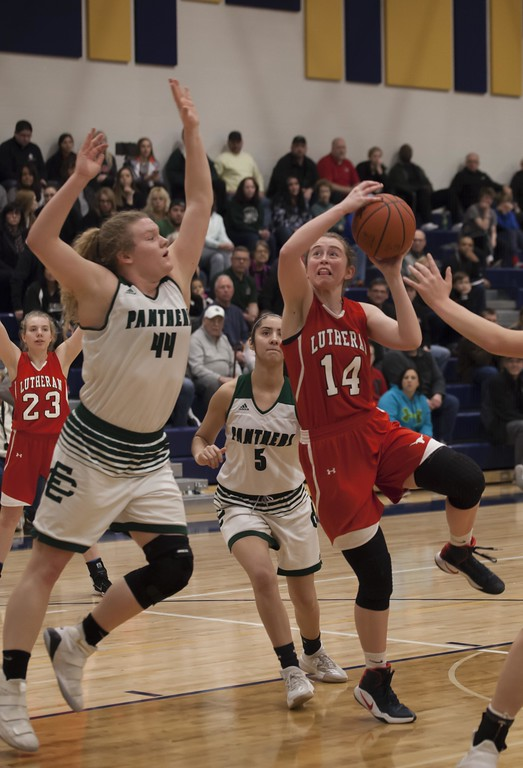 . Jen Forbus - The Morning Journal<br> Lutheran West\'s Carleen Ellerbruch prepares to shoot as Elyria Catholic\'s Ally Winnen takes aim to block in the Division III North Ridgeville District final on March 3.