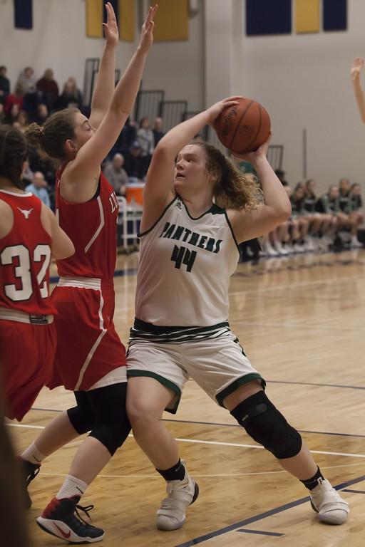 . Jen Forbus - The Morning Journal<br> Ally Winnen of Elyria Catholic looks for a way around Lutheran West\'s Carleen Ellerbruch during the Division III North Ridgeville District final on March 3.