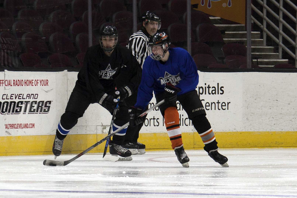 . Jen Forbus - The Morning Journal Midview\'s Heath Naso challenges Gage Stanley of North Canton Hoover for possession of the puck during the GCHSHL All-Star hockey game on March 4 at the Quicken Loans Area.