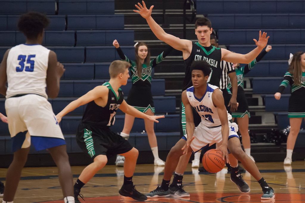 . Jen Forbus - The Morning Journal<br> Lutheran East\'s Davyon Adams looks to his team for assistance as Columbia\'s Josh Borling and Charlie Simon close in on him in the key on March 5.