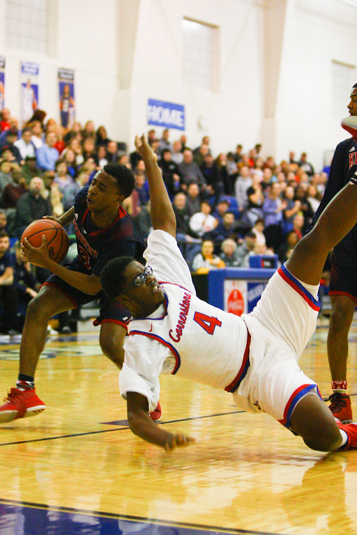 . David Turben - The News-Herald 2018 - Basketball - Orwell District - Cornerstone vs JFK.  Cornerstone defeated JFK 72-56.  Cornerstone\'s Jeremy Owens (4) gets fouled hard while going up for a shot by JFK\'s Terrance King (3).