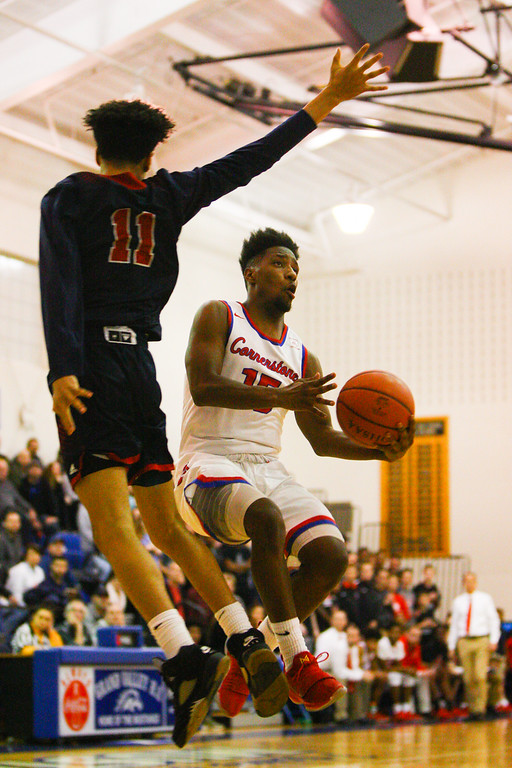 . David Turben - The News-Herald 2018 - Basketball - Orwell District - Cornerstone vs JFK.  Cornerstone defeated JFK 72-56.  Cornerstone\'s Dontavius McQueen (15) makes a move mid-air to get a shot off against JFK\'s Sharrod Taylor (11).