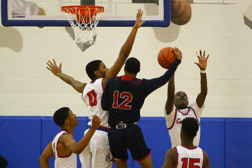 . David Turben - The News-Herald 2018 - Basketball - Orwell District - Cornerstone vs JFK.  Cornerstone defeated JFK 72-56.  JFK\'s Byron Taylor (12) goes up for a shot against a tough defense by Cornerstone\'s Kendall Saunders (0) and Martel Ferrell (1).