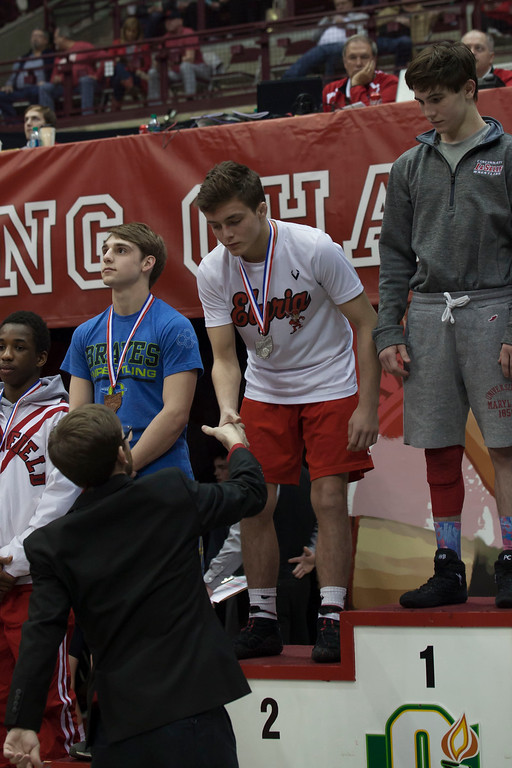 . Jen Forbus - The Morning Journal<br> Dylan Shawyer of Elyria is presented his runner-up medal on the winner\'s podium Saturday night at the state wrestling tournament.