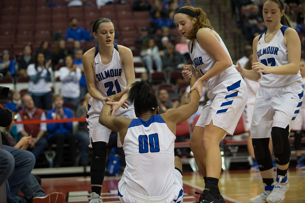 . Michael Johnson - The News-Herald Gilmour Academy\'s Annika Corcoran (21) and Emily Kelley (4) help up Naz Hillmon (00) off the court during the 2017 OHSAA Girls State Final game at the Schottenstein Center in Columbus on March 18.  The Gilmour girls Basketball team defeated the Versailles Tigers 56-54 to become State Champions.