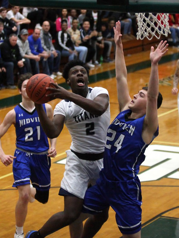 . Randy Meyers - The Morning Journal<br> Lorain\'s Taevon Pierre-Louis shoots over Midview\'s Vince Birth during the first quarter of a district semifinal on March 7.