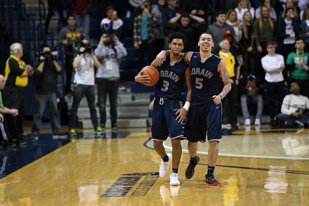. Eric Bonzar�The Morning Journal<br> Devone Grant (3) and David Weatherington walk the court after knocking off Toledo St. John\'s 47-44 in the Division I District Championship game, March 17, 2018.