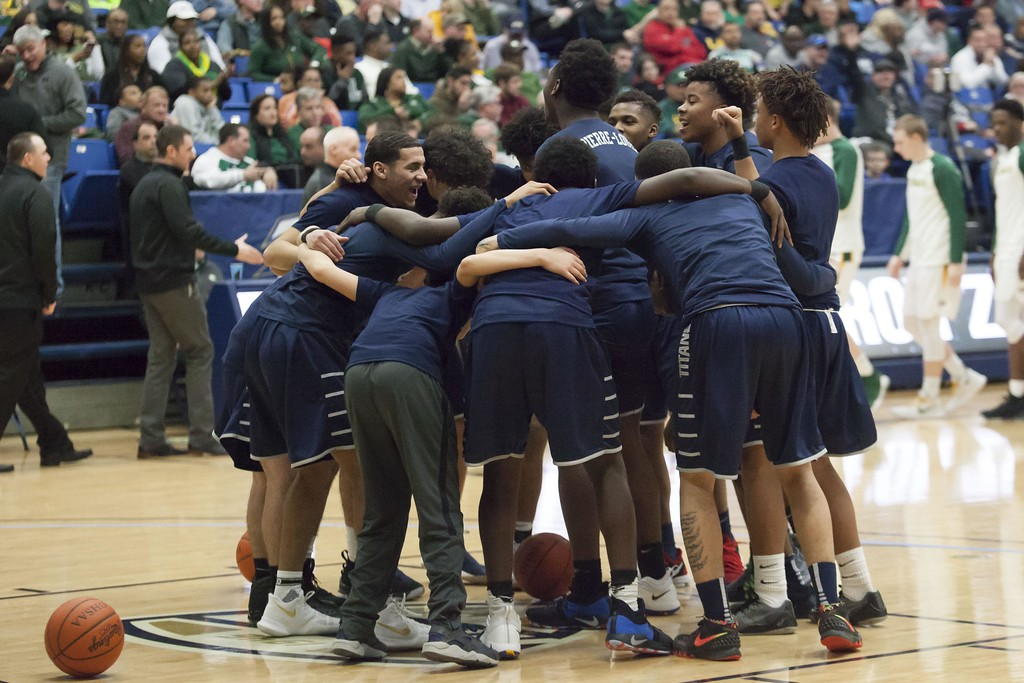 . Jen Forbus - The Morning Journal<br> The Lorain Titans basketball squad comes together before the start of a regional semifinal contest against St. Edward.