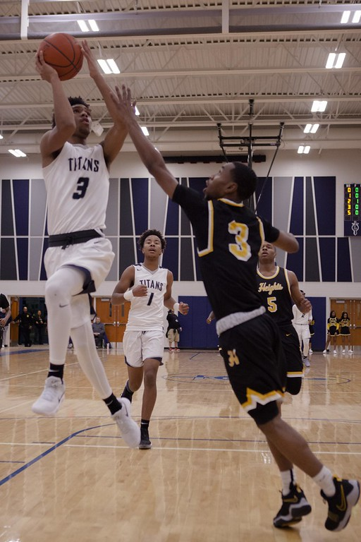 . Jen Forbus - The Morning Journal<br> Cleveland Heights guard Yahel Hill tries to block Lorain guard Devon Grant\'s shot on Jan. 18.