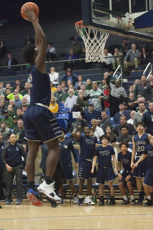 . Jen Forbus - The Morning Journal<br> Taevon Pierre-Louis takes aim to lay down a dunk against St. Edward.