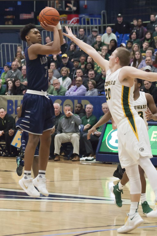 . Jen Forbus - The Morning Journal<br> St. Edward\'s PJ Flannery attempts to defend as Lorain\'s Devon Grant pops a shot from the three-point range.