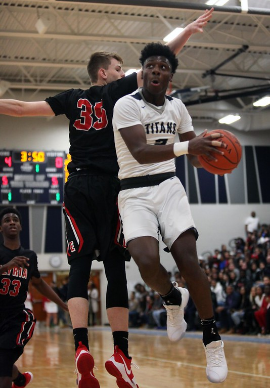 . Randy Meyers - The Morning Journal<br> Lorain\'s Taevon Pierre-Louis drives up and under Elyria\'s Justin Koepp for the shot during the first quarter on Dec. 29.