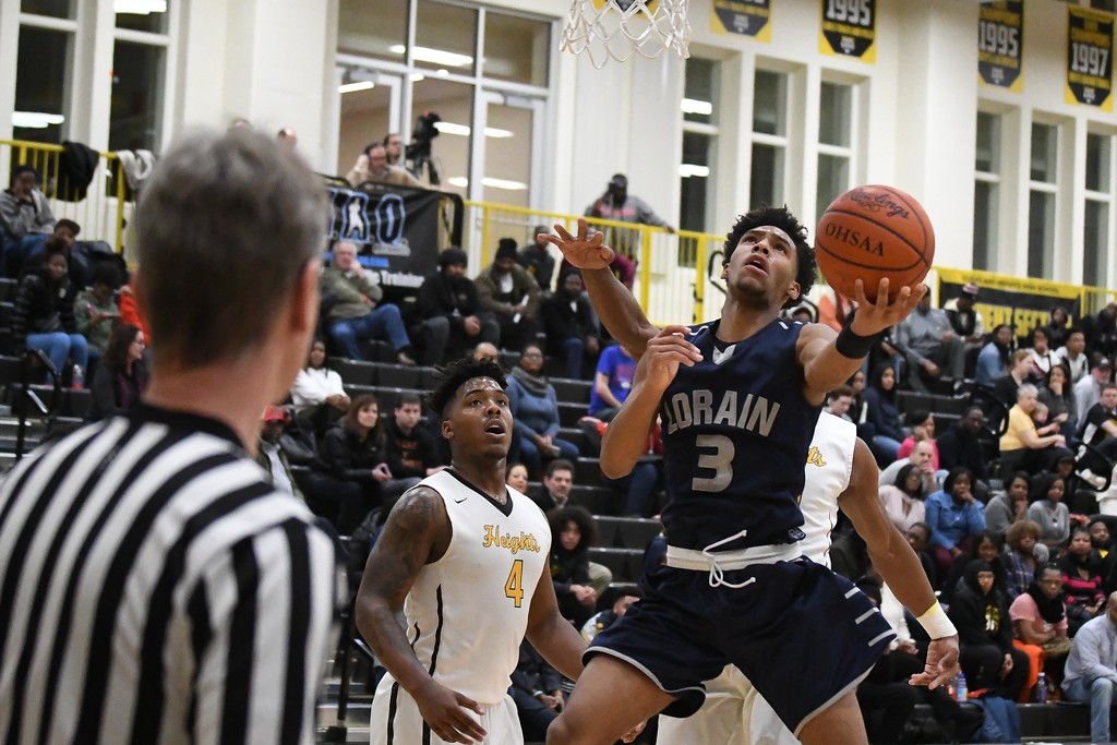 . Eric Bonzar�The Morning Journal<br> Lorain guard Devon Grant splits the Cleveland Heights defense on his way to the basket.