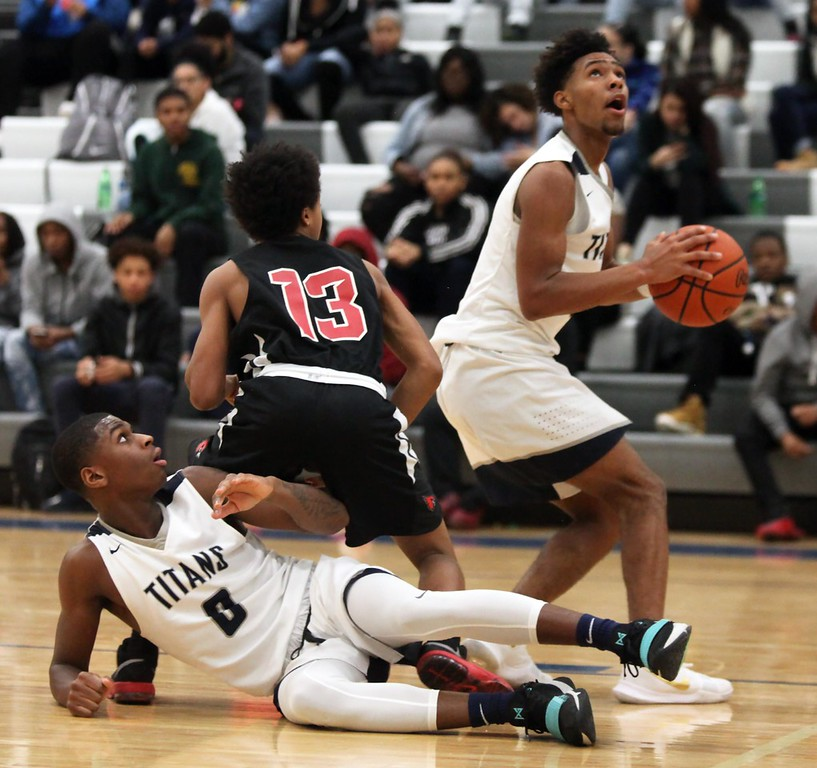 . Randy Meyers - The Morning Journal<br> Shaw\'s Lugman Lateef loses the ball to Devon Grant of Lorain on Feb. 2.