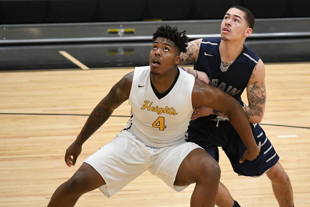 . Eric Bonzar�The Morning Journal<br> Lorain guard David Weatherington is boxed out under the rim by cleveland Heights forward Tyreke Smith.