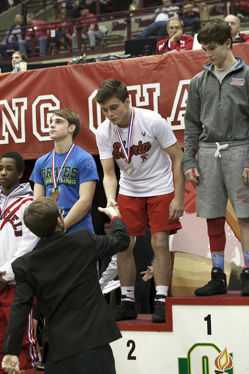 . Jen Forbus - The Morning Journal<br> Dylan Shawyer of Elyria is presented his runner-up medal on the podium Saturday night at the state wrestling tournament.