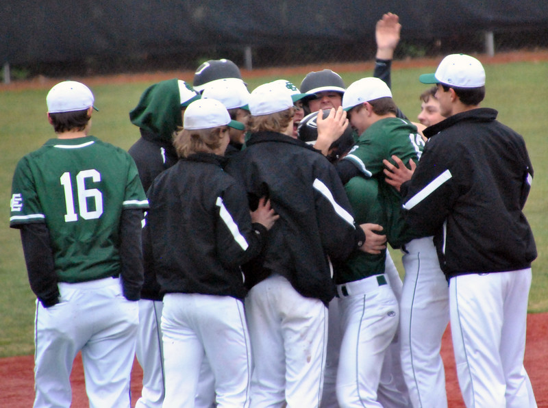 Jon Behm - The Morning Journal<br /> Elyria Catholic teammates mob Ryan Strittmather following his walk-off single against Vermilion on March 28 at Oberlin College.