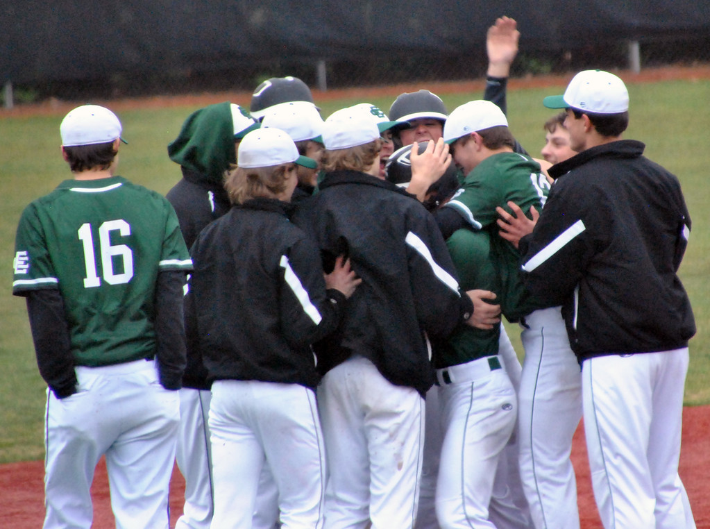 . Jon Behm - The Morning Journal Elyria Catholic teammates mob Ryan Strittmather following his walk-off single against Vermilion on March 28 at Oberlin College.