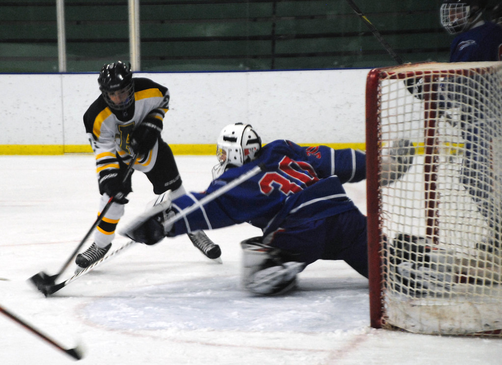 . Jon Behm - The Morning Journal<br> Amherst sophomore Jacob Kramer works to get the puck around Bay goalie Sean Gulley during the first period of a Baron Cup II quarterfinal on Feb. 5 at Brooklyn\'s John M. Coyne Recreation Center.