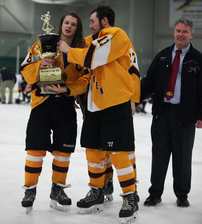 . Randy Meyers - The Morning Journal<br> Avon Lake\'s Timothy Lubertozzi hands the Baron Cup III trophy over to Jared Aslaksen as coach Fran Sullivan looks on after winning the championship Feb. 11.