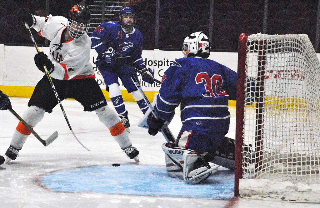 . Jon Behm - The Morning Journal<br> North Olmsted\'s Riley Vertosnik cuts the puck through the crease as Bay goalie Sean Gulley works to make a save during the second period on Dec. 22. Vertosnik had a hat trick in the Eagles\' victory.