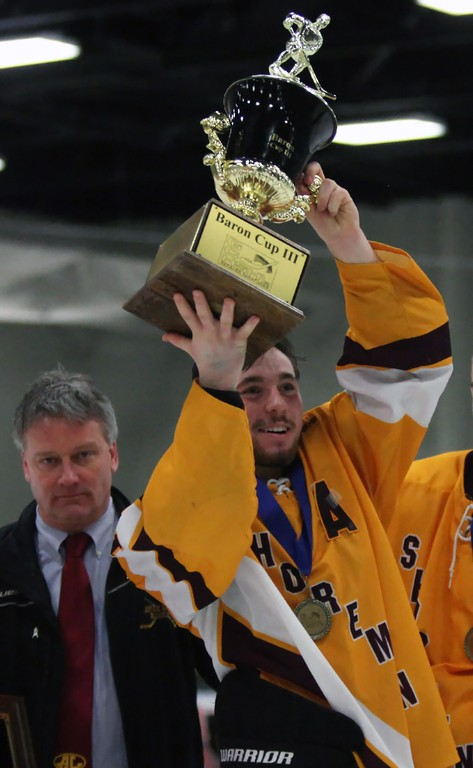 . Randy Meyers - The Morning Journal<br> Timothy Lubertozzi hoists the Baron Cup III trophy after his team defeated Normandy for the title on Feb. 11.