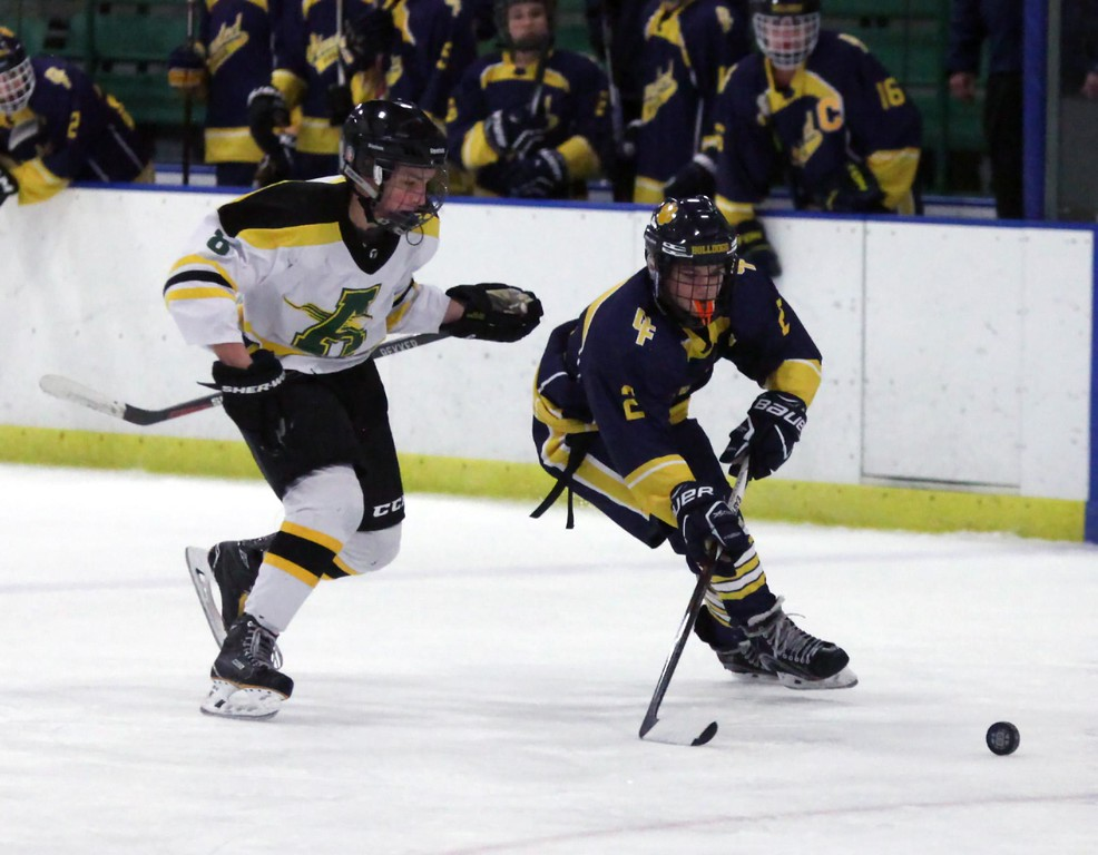 . Randy Meyers - The Morning Journal<br> Alex Kerkay of Olmsted Falls and Nathan Harmych of Amherst go after a rolling puck during the first period of the Baron Cup II final on Feb. 11.