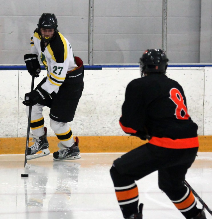 . Randy Meyers - The Morning Journal<br> Michael Giannuzzi of Amherst moves the puck away from his goal and towards Jake Hirz of North Olmsted during a Southwestern Conference tournament semifinal on Jan. 15.